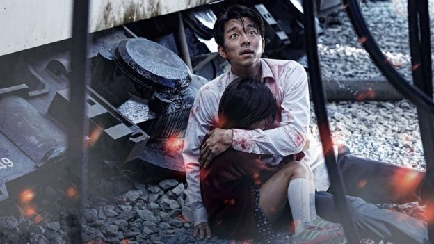 A still from Train to Busan with two characters cowering in fear next to a train.