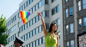 A Latina waving a pride flag.