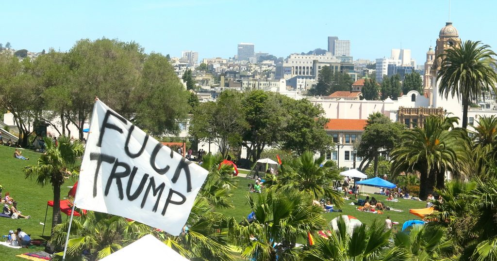 A flag reading FUCK TRUMP waving over Dolores Park in San Francisco.