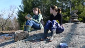 Two young people reading outdoors.