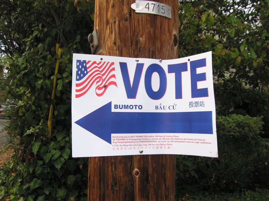 A sign pointing towards a polling place.
