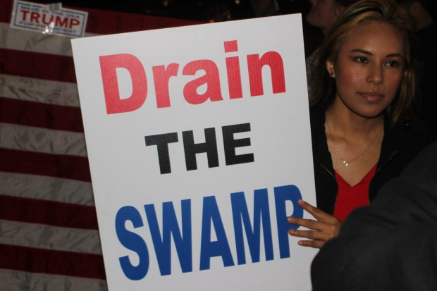 Trump supporter Sara Burno holding up a DRAIN THE SWAMP sign.