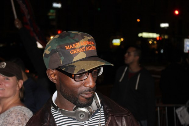 A Black Trump supporter in a camo MAKE AMERICA GREAT AGAIN hat.