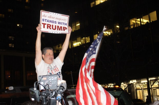 A Trump supporter waving a sign from the back of a car.