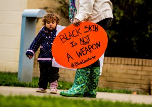 A parent and child holding a sign informing the reader that Black skin is not a weapon.