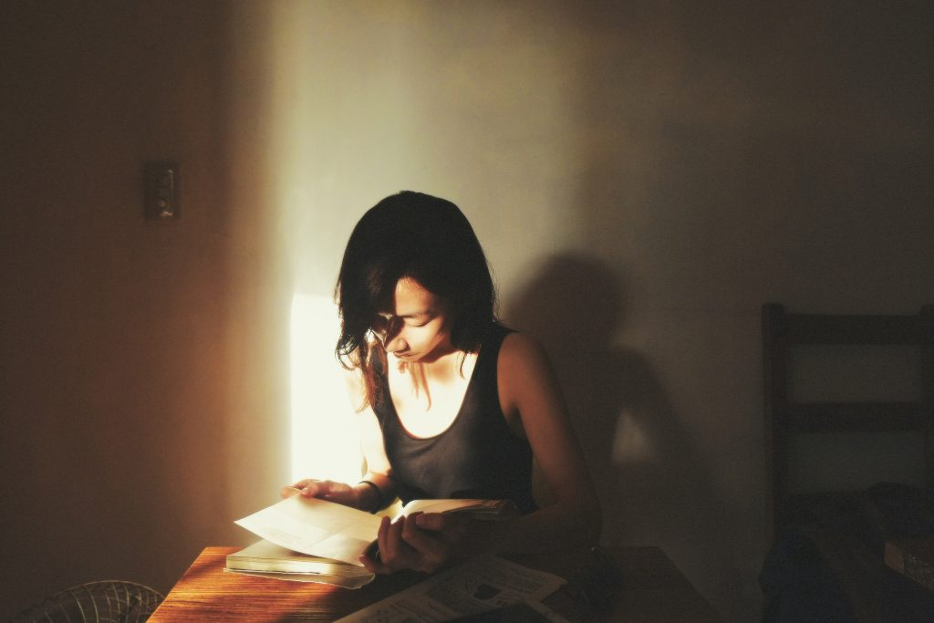 A person reading at a table, highlighted in a shaft of light.