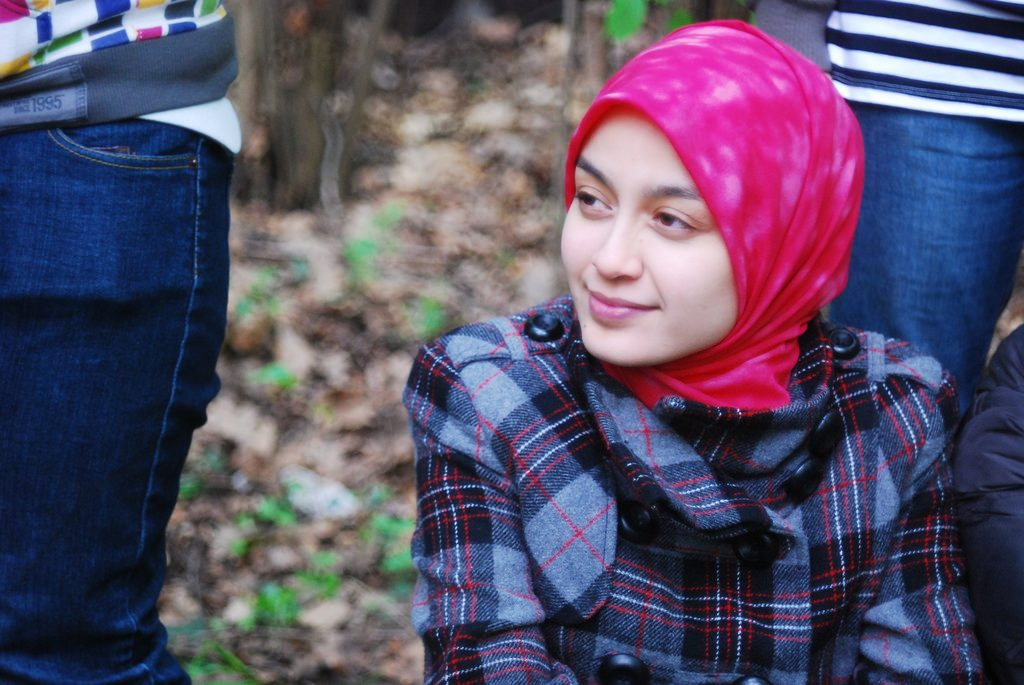 A smiling woman wearing a headscarf.