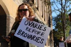 A person holding up an ovaries before brovaries sign.