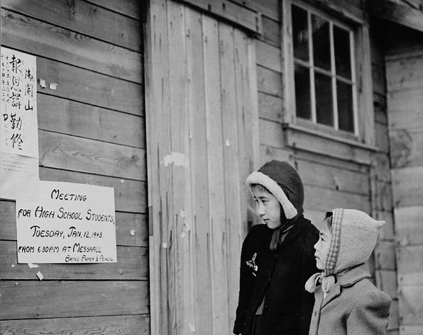 Japanese-Canadian children read a sign posted at the schoolhouse in their internment camp.