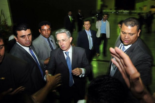 Colombian President Alvaro Uribe greets the public while flanked by bodyguards