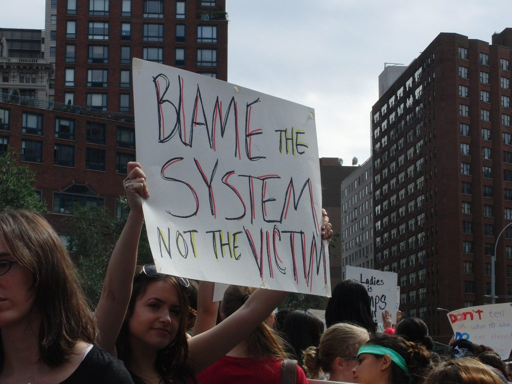A protester holds up a sign: Blame the system, not the victim.