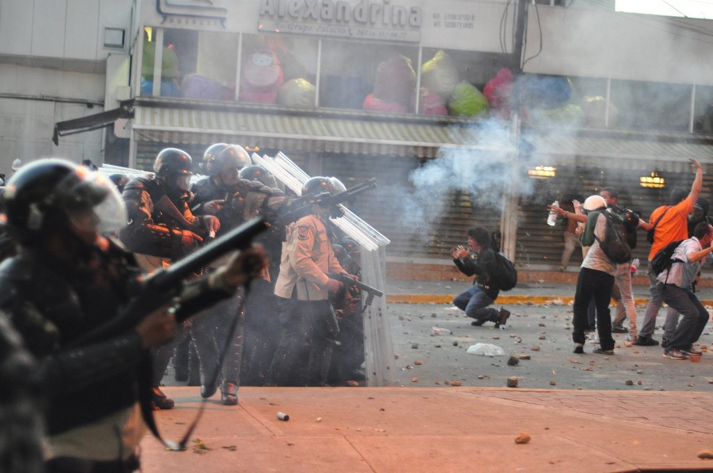 A crowd of protesters being dispersed by police in Venezuela.