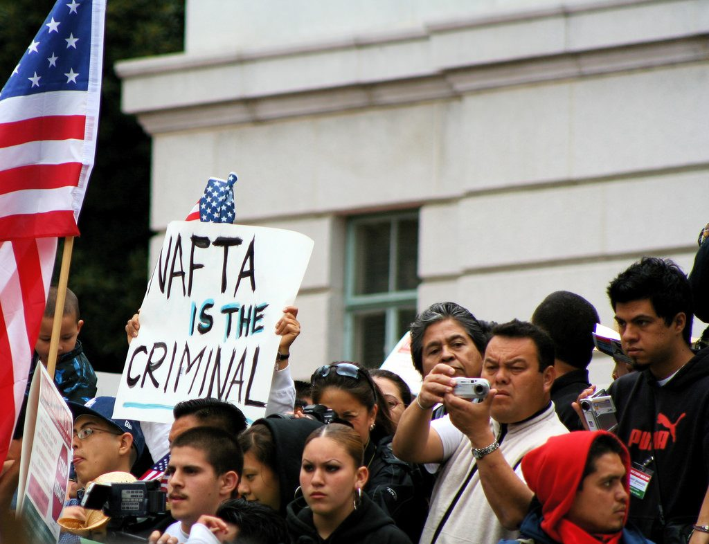 A protester holding up a sign: NAFTA IS THE CRIMINAL