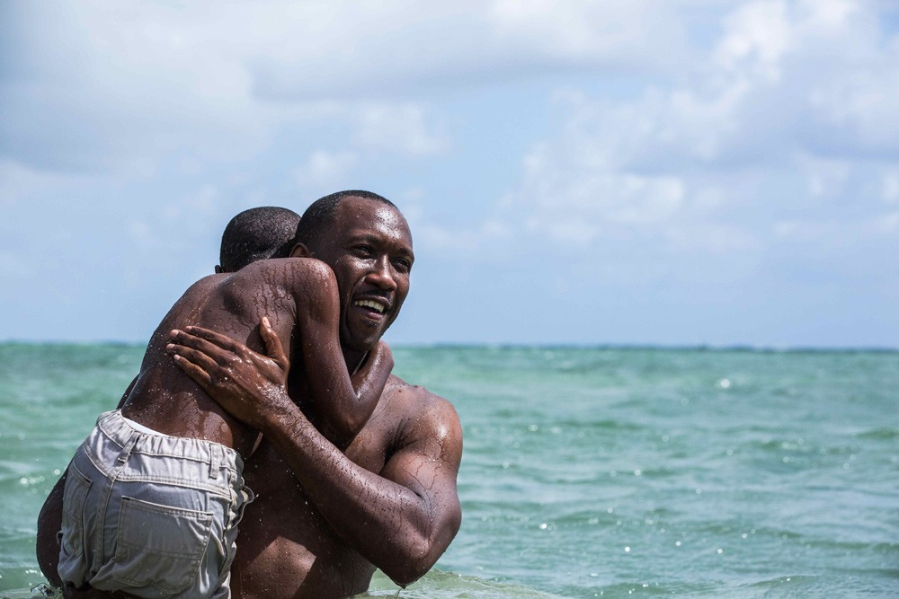 A still from Moonlight, featuring a Black man emerging from the ocean, holding a boy over his shoulder.