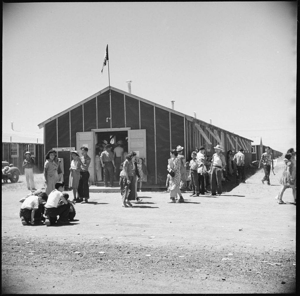 A black and white photo of Japanese internees at Tule Lake milling aound a flimsy building.
