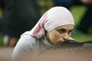 A woman in hijab leaning forward to rest her nose on a chair.