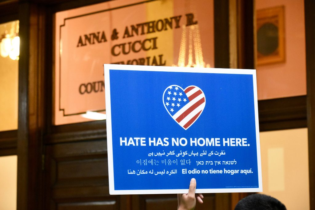 A protester holding up a HATE HAS NO HOME HERE sign.