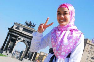 A woman in a bright pink hijab, smiling and making a peace sign.
