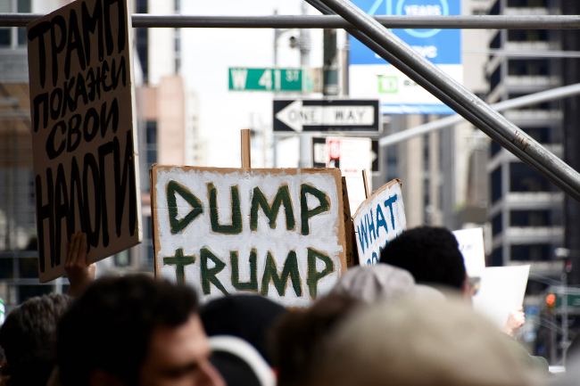 A protester holding a dump trump sign on a crowded sidewalk.
