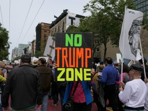Protesters holding up a NO TRUMP ZONE sign