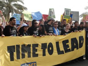 Protesters carrying a TIME TO LEAD sign