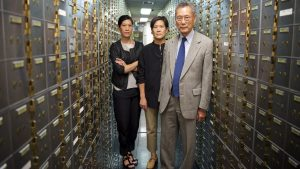 A still from the documentary Abacus showing three Chinese-Americans standing in a bank vault