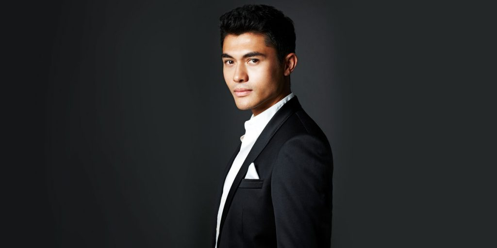 A promotional still of Henry Golding, a Eurasian actor wearing a suit.