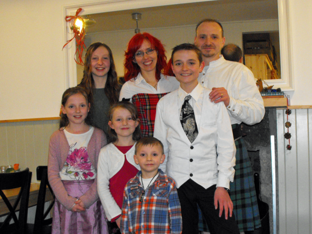 A smiling white family wearing tartans.