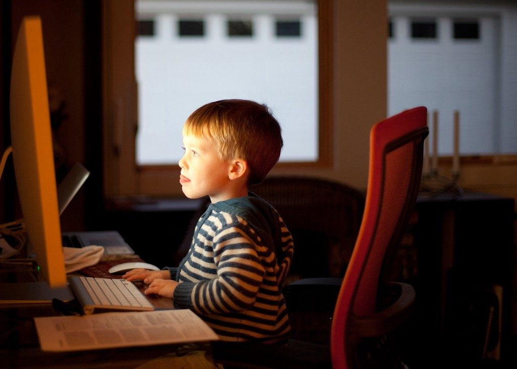 A young child staring into a computer screen.