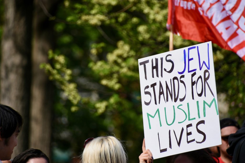 A protester holds a sign: THIS JEW STANDS FOR MUSLIM LIVES
