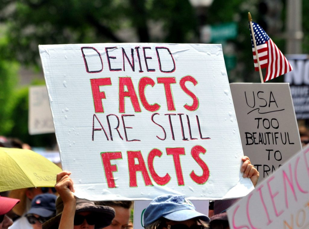 A protest sign: DENIED FACTS ARE STILL FACTS.