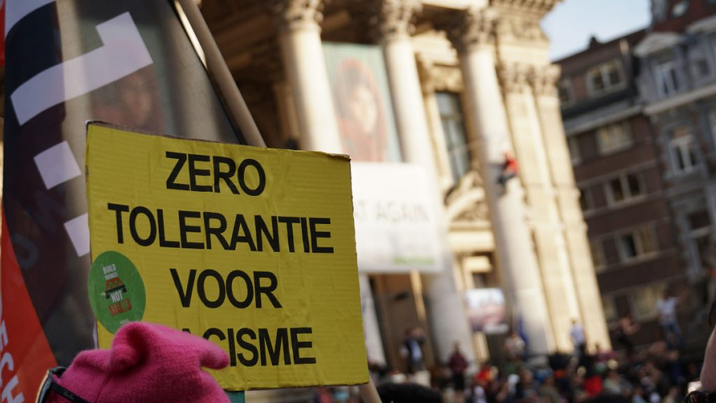 Protesters in Brussels holding up a sign.