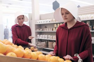 A still from the Handmaid's Tale, showing a woman in red with a dramatic white head covering.