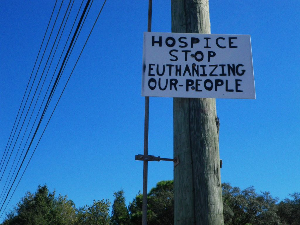 A sign: HOSPICE STOP KILLING OUR PEOPLE