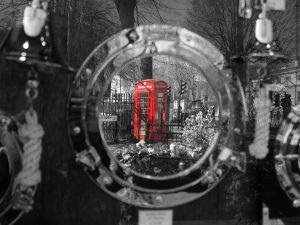 A classic red phone booth reflected in a mirror.