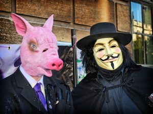 A man dressed in a suit and pig mask accompanied by someone dressed as V from V for Vendetta.