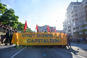 G20 protesters carrying a SHUT DOWN CAPITALISM sign
