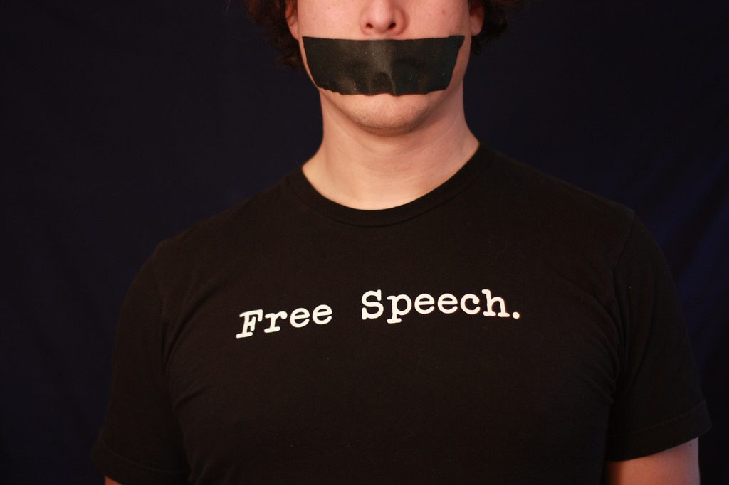 A person wearing a shirt that says FREE SPEECH, with tape over their mouth