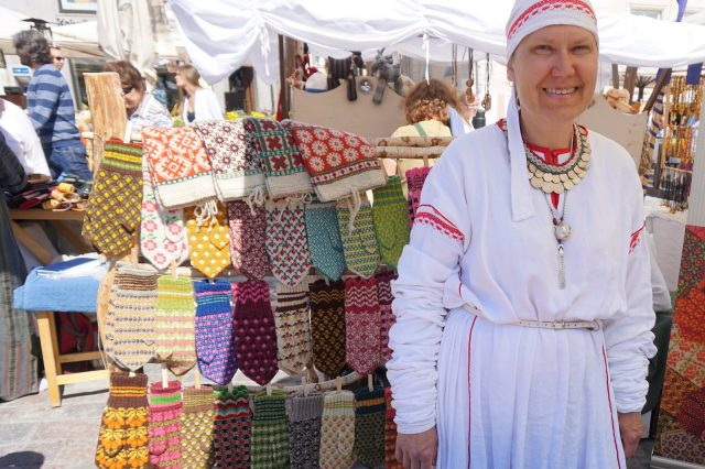 A smiling Estonian woman with handknit goods.