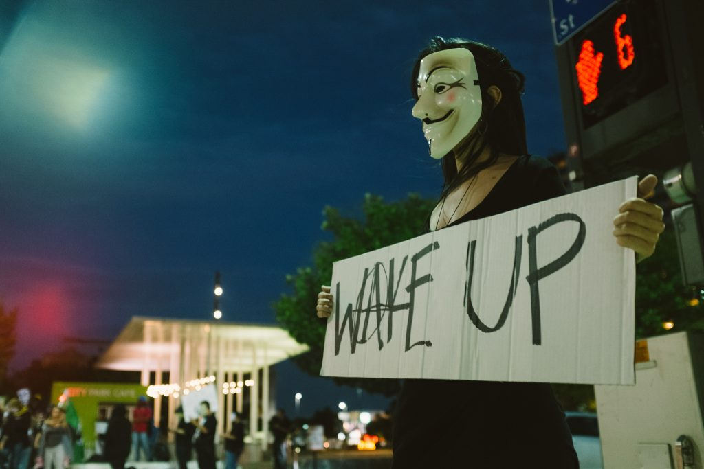 A protester in an anonymous mask carrying a sign that says WAKE UP