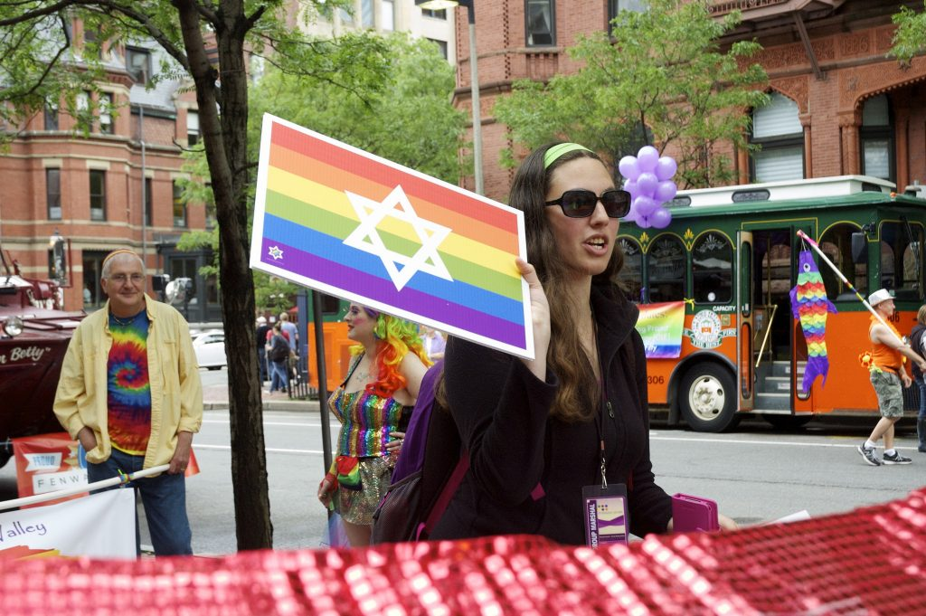 A marcher at Pride carrying a rainbow flag with a star of David