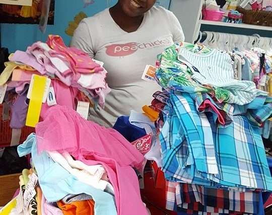 A smiling woman holding up clothing donations.