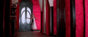 A still from Suspiria, featuring a woman in a flowing gown running down a hall