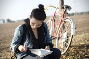 A person sitting on the ground next to a bicycle, reading a book.