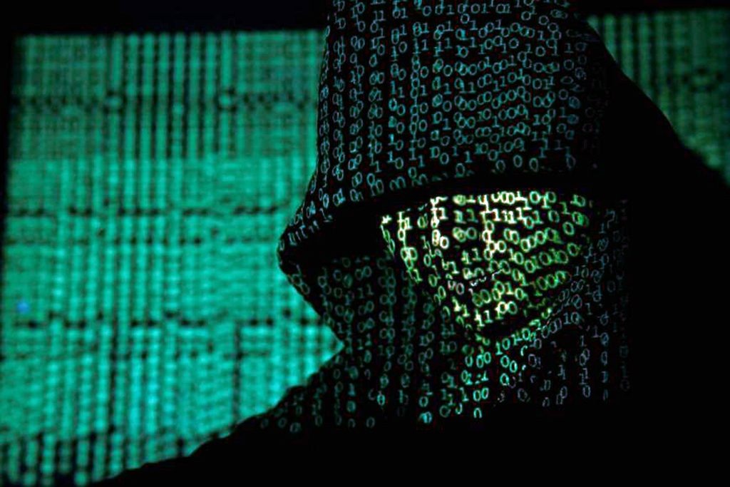 A person in a hooded garment, with binary code projected on their body