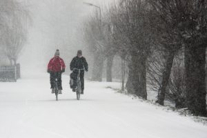 Two cyclists on a snowy day.