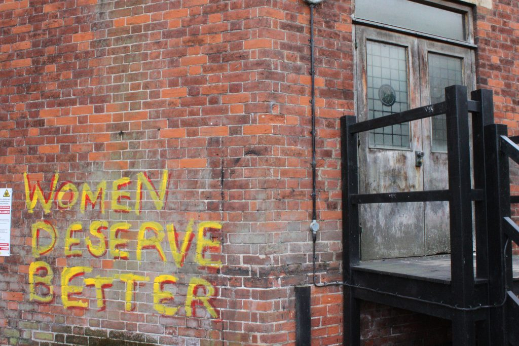 A wall emblazoned WOMEN DESERVE BETTER