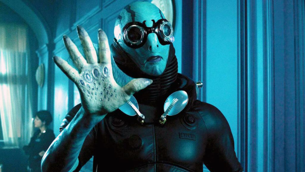 A still from the shape of water featuring an eerie humaoid figure communicating in sign language