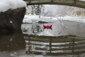 A red paper boat under a bridge over a frozen river.