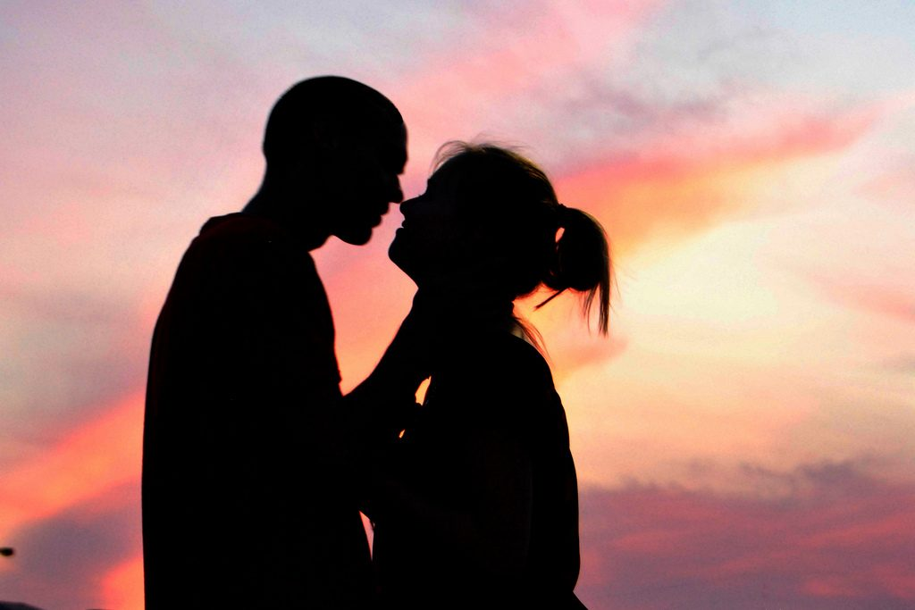 A couple kissing at sunset.
